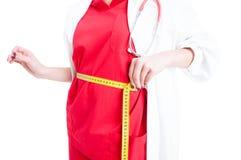 测量她的腰部的女性医生特写镜头 免版税图库摄影