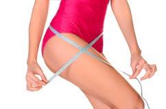 测量她的腰部的年轻运动的妇女 免版税库存照片