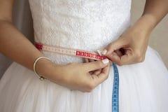 测量她的腰部的新娘在婚礼之日前 图库摄影
