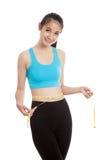 测量她的腰部的美丽的亚裔健康女孩 库存图片