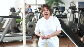测量她的腰部的资深妇女在健身房 股票录像