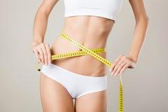 测量她的腰围的妇女。完善的亭亭玉立的身体 免版税库存照片