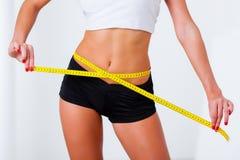 测量她的腰围的白肤金发的妇女 免版税图库摄影