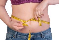 测量她的腹部油脂的妇女 免版税图库摄影