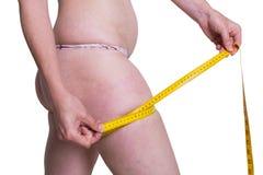 测量她的腿的肥胖妇女 库存图片