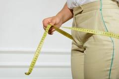 测量她的臀部的妇女由磁带 免版税库存图片