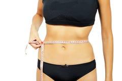 测量她的臀部的年轻可爱的妇女 库存照片