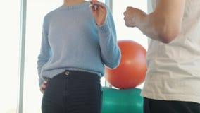 测量年轻女人的腰部的医生 影视素材
