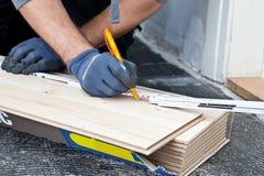 测量新的木地板的木匠 库存图片