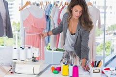 测量时装模特的时装设计师 免版税库存照片