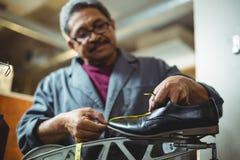 测量有措施磁带的鞋匠一双鞋子 库存照片