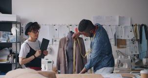 测量服装和一起使用片剂工作的创造性的设计师在演播室 股票录像