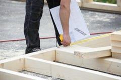 测量木墙壁结构的监督员 免版税库存图片