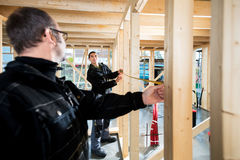 测量木柱子的木匠在站点 免版税图库摄影