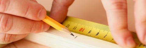 测量木酒吧特写镜头的工作者的胳膊 免版税图库摄影