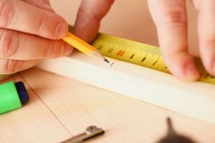 测量木酒吧特写镜头的工作者的胳膊 免版税库存图片