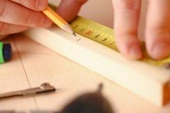测量木酒吧的工作者的胳膊 免版税库存图片