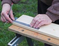 测量木头的木匠业 免版税库存照片