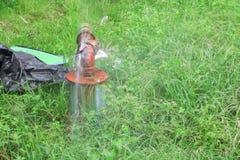 测量深度主要管和水泄漏,老在草地板上的轻拍管子钢铁锈 免版税库存照片