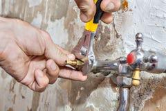 测量深度工作,在手中修理龙头,特写镜头可调扳手 免版税库存图片