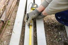 测量混凝土桩的建筑工人 免版税库存照片