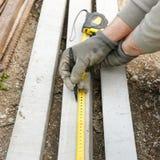 测量混凝土桩的建筑工人 免版税库存图片