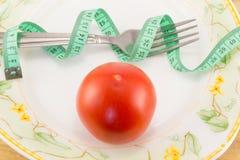测量的磁带和一把叉子用蕃茄 库存图片