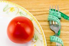 测量的磁带和一把叉子用被隔绝的蕃茄 免版税图库摄影
