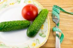 测量的磁带和一把叉子用被隔绝的蕃茄 免版税库存照片