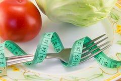 测量的磁带和一把叉子用被隔绝的蕃茄 图库摄影