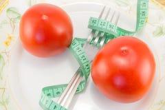 测量的磁带和一把叉子用被隔绝的蕃茄 库存照片