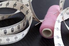 测量的磁带和缝纫针在螺纹短管轴  免版税图库摄影