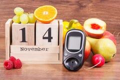 测量的糖水平的日期11月14日作为世界糖尿病天的标志的,与菜的glucometer和果子 库存图片