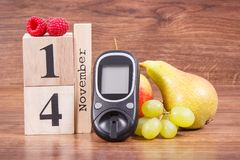 测量的糖水平的日期11月14日作为世界糖尿病天的标志的, glucometer和果子 库存照片