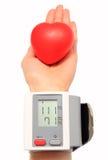 测量的血压和红色心脏在手中 免版税库存照片
