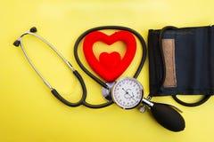测量的血压的Tonometer与一个健康听诊器的概念和在黄色背景的红色心脏 库存图片
