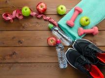 测量磁带毛巾和瓶水的运动鞋哑铃 免版税库存图片