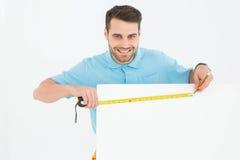 测量空白的广告牌的愉快的工作者 免版税库存图片