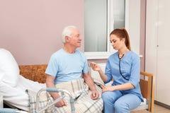 测量老人的温度的护士 医疗协助 库存图片