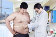 测量耐心肥胖病的医生 免版税库存照片