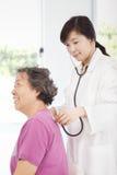 测量资深妇女血压的家庭医生 免版税库存照片