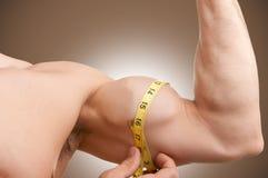 测量他的二头肌 库存照片