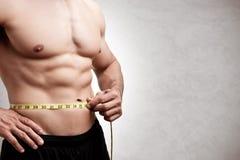 测量他的腰部的适合的人 免版税库存照片