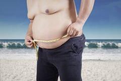 测量他的腹部的肥胖人 库存图片