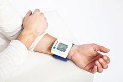 测量他的血压的年轻man's手 免版税库存图片