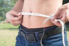 测量他的身体的健康人 播种的和中央部位图象  免版税库存图片