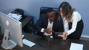 浏览一种数字式片剂的企业夫妇互联网在办公室 免版税图库摄影