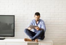 浏览与片剂的愉快的人在家坐洗脸台 免版税库存图片