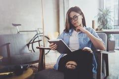 浏览与触摸屏设备的年轻美丽的行家妇女在现代coworking的工作地点 免版税库存图片