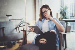 浏览与触摸屏设备的年轻美丽的行家妇女在现代coworking的工作地点 库存图片